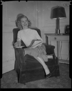 Barbara Ann Scott seated with glass and newspaper in hotel room at Copley Plaza