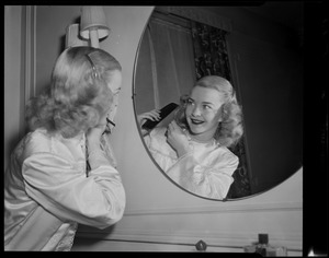 Barbara Ann Scott combing her hair in mirror