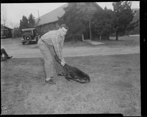 Man holding beaver by tail