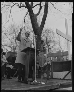 Billy Graham speaking at outdoor podium with large cross nearby