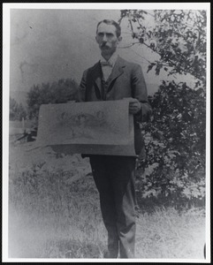 Young man holding a large paper, possibly a large map or blueprints
