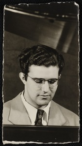 Young man with glasses and curly hair looking down