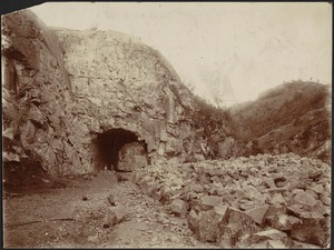 Arched tunnel through side of mountain, two men standing inside