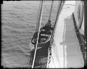 View from large vessel of small boat hanging from davits alongside