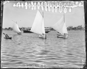 "Charles W. Parker kayaking alongside three sailing dories with ""Herald"" in background"