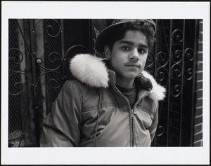 Young man wearing baseball cap stands in front of gate, probably Green Street, Jamaica Plain