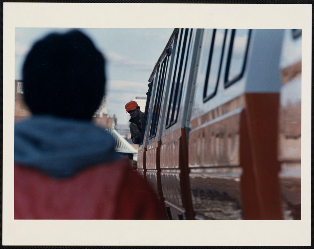 Man with orange baseball cap leans out of a Orange Line train