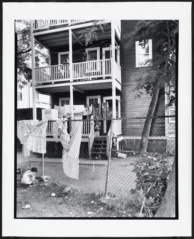 Laundry hangs off of a line on a back deck and a chain link fence