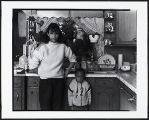 Boy and young woman stand in kitchen