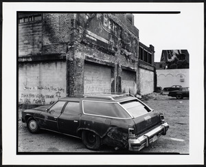 Car parked in front of graffitied building