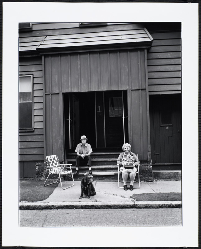 Man and woman sits in front of doors with dog