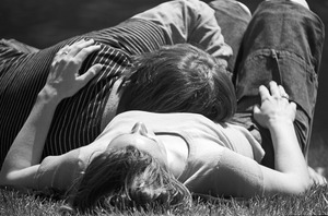 Couple relax in sun on Charles River embankment, Boston