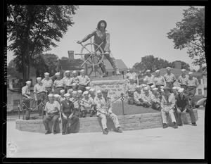 Sailors sit with Fishermen's Statue in Gloucester