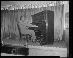 Black piano player (possibly at The Handy Café)
