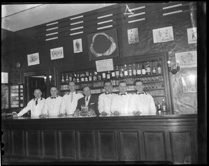 Bar staff poses under shark jaw
