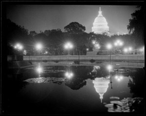 U.S. Capitol at night, reflected in pool