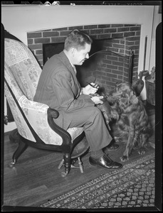 Unident. man with dog in front of fireplace
