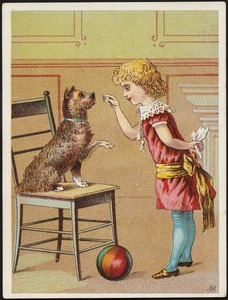 A girl playing with a dog on a chair who is lifting its paw, with a ball in the foreground.