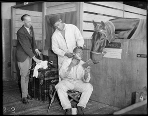 Behind the curtain at the Boston Horse Show, Boston Garden, a groom gets a shave and a haircut