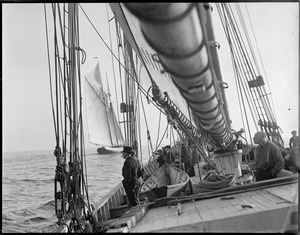 Glimpse of the fishing schooner Columbia through rigging of the Elizabeth Howard.