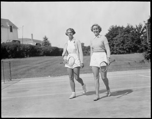 2 women carrying tennis rackets