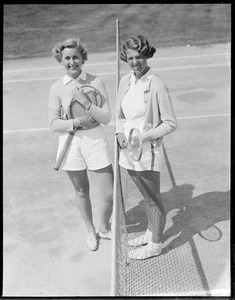 2 women carrying rackets