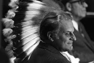 Billy Graham juxtaposed with Indian head dress, Plymouth