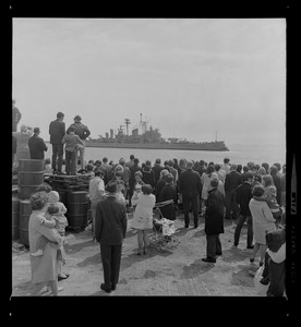 As the Boston-based USS Boston sails out of Boston Harbor for another tour of duty in Vietnam, tear-filled wives, friends and relatives of the crew wave their farewells from docks of the South Boston Naval Annex