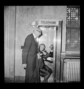 Dr. and Mrs. Benjamin Spock speak on telephone with their grandchildren on opening day of trial