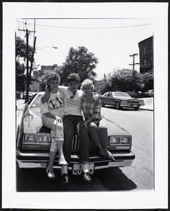 Two women and a man sit together on the hood of a car