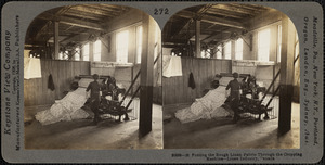 Putting the rough linen fabric through the cropping machine - linen mill.