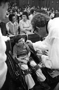 Crippled boy receives communion at orphanage mass, Brighton