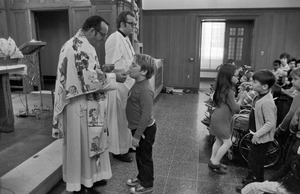 Boy receives communion at orphanage mass, Brighton
