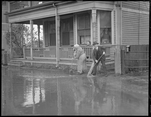 Couple attempts to sweep water away from their cellar as surf from nor'easter floods Winthrop