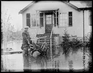 Man with wheelbarrow in flooded yard, New England flood