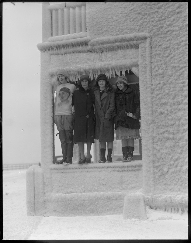 Ethel M. Padden, Blanche Rupp, Elinor Rourke, and Anna Shapiro stand in porch of ice covered house on Shore Drive, Winthrop
