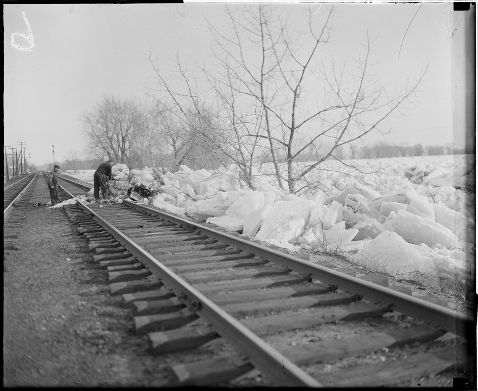 Clearing ice off railroad tracks, during flood
