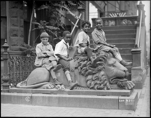 South End kids pose on stone lion, 511 Columbus Ave.