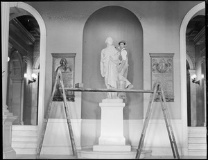 Robert J. Guthrie cleaning the George Washington statue in the State House for the bicentennial of Washington's birth