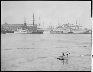 Two boys on homemade raft, Boston Harbor, Navy Yard behind them