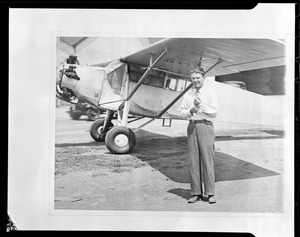 Douglas P. Corrigan, 31, of Los Angeles, standing beside his 1929 model plane in which he recently made a non-stop transcontinental flight from Long Beach. His expenses for the trip were $110.05 - the five cents for a chocolate bar.
