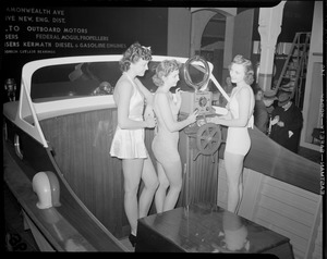 Bathing beauties aboard motor boat at boat show