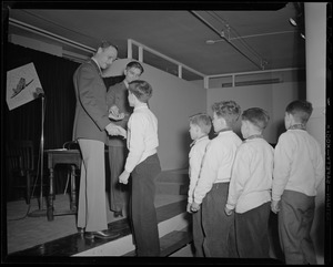 Boys' Clubs of Boston members line up to receive Victory Volunteers badges from Col. George A. Ford and Pfc. Hy Rosen at Jordan Marsh Co. Auditorium