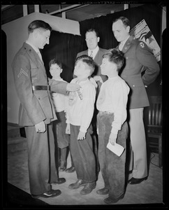 Boys' Clubs of Boston members receive Victory Volunteers badges from Pfc. Hy Rosen while Col. George A. Ford and Frederic C. Church, Jr., watch at Jordan Marsh Co. Auditorium