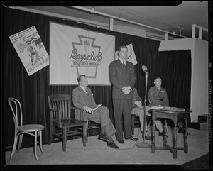 Boston Mayor Maurice Tobin speaks at induction of Boys' Club of Boston members into the Victory Volunteers while Frederic C. Church, Jr., Col. George A. Ford, and Pfc. Hy Rosen watch at Jordan Marsh Co. Auditorium