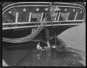 Outrigger rowboat under stern of USS Constitution