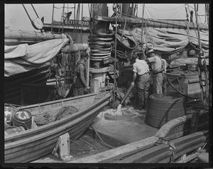 Tugs pumping water out of hold of fishing schooner to prevent her from sinking at T-wharf
