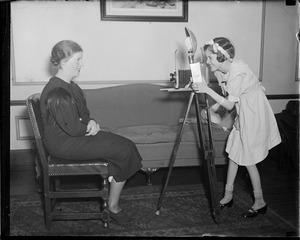 Alyce Jane McHenry turns news cameraman, while Dolores Crispo, her favorite Nurse, poses at the Nurses Home, Fall River