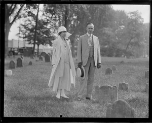 Calvin and Mrs. Coolidge stand next to grave stone