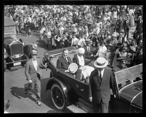 Pres. and Mrs. Coolidge rushing through Plymouth, MA. Cheering crowds bring rare smile to President.